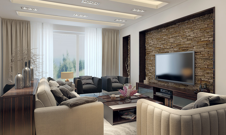 Family living room decorated sofas in black and beige, coffee table, wall cladding & false ceiling looks luxurious.