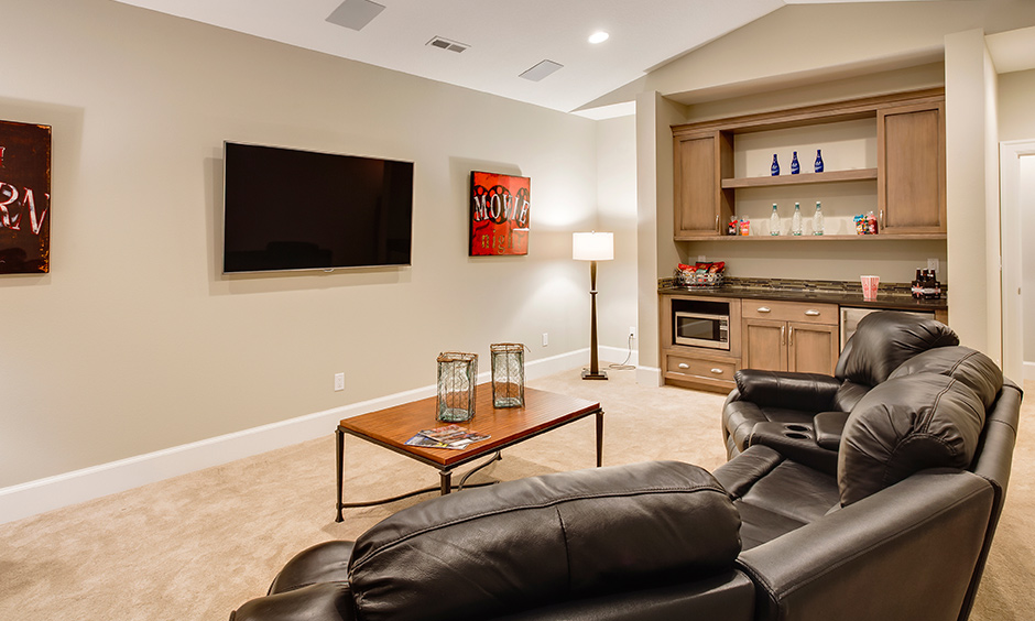 Family room decor ideas replace the traditional sofa with reclining sofa and modern coffee table to bring theatre vibes.