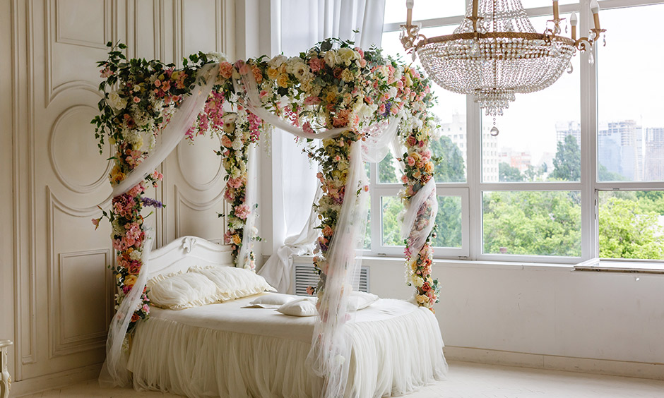 Four poster bed curtains decorated with a fresh flower in the white bedroom brings a touch of flowing beauty.
