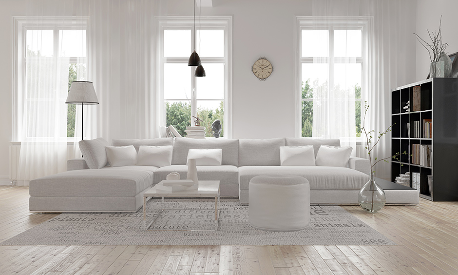 Sectional u-shaped white leather sofa in this white living room is perfect for a big family.