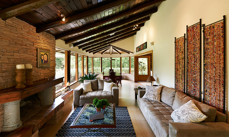 Modern farmhouse style living room with large wooden windows, wooden ceiling, sofas and coffee table brings old-world charm.