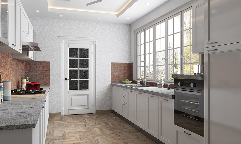 White coloured open cabinets and the countertop attached beside the window made in a very small space of a small parallel kitchen design in india