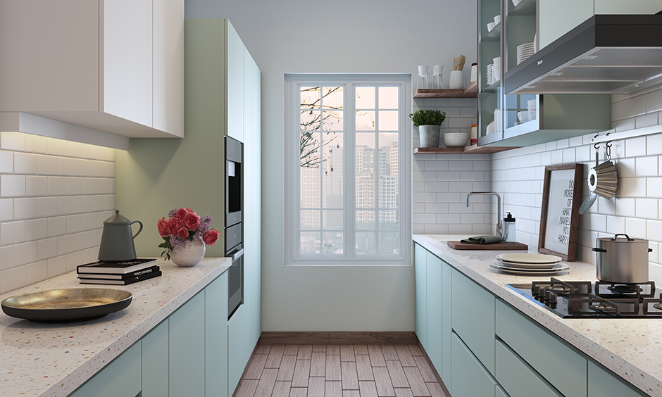 A cosy and lovely pink coloured cabinet attached beside the window on wall cabinets of a small parallel kitchen design