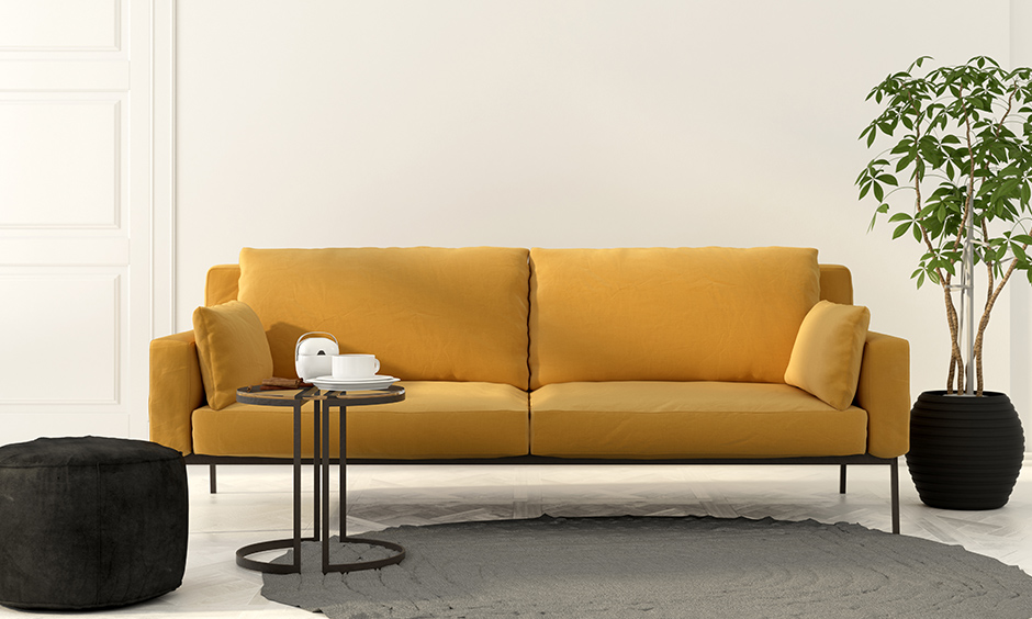 Mustard yellow upholstery sofa works well on walls with light colours in this white room.