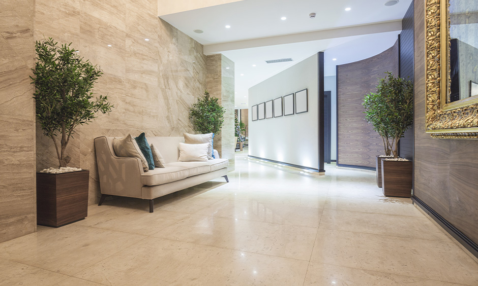 This lobby decoration in the passageway with indoor plants, sofa & false ceiling with recessed lighting is gorgeous.