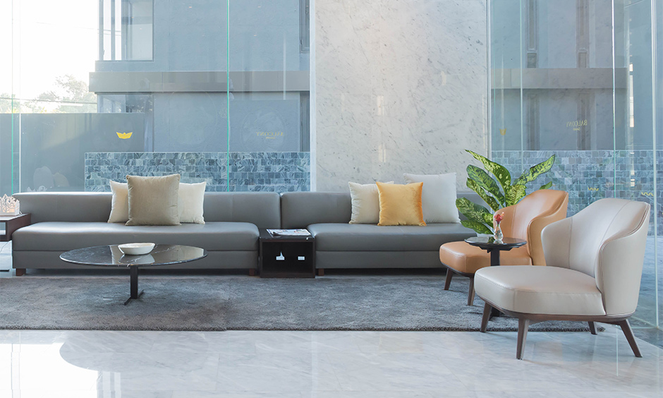 A lobby interior designed with a pop of colour, grey sofa and a tea table is elegant with a large glass window.