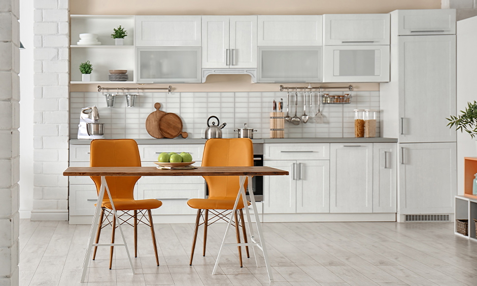 Small kitchen design with dining table foldable one with amber coloured chairs looks minimal yet stylish.