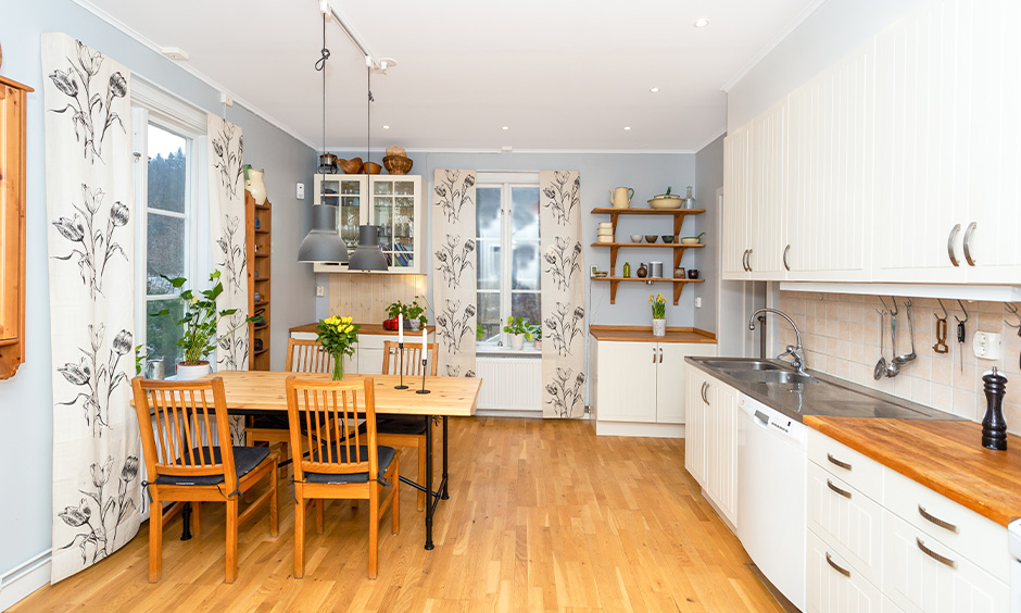 Two hanging light above the wooden dining table with matching chairs looks rustic is the kitchen with dining table ideas
