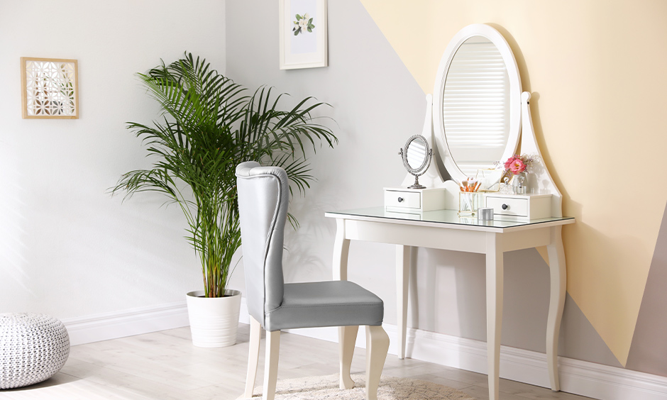 Victorian-styled white wooden dressing table designs with oval mirror, a console table & drawers look elegant.
