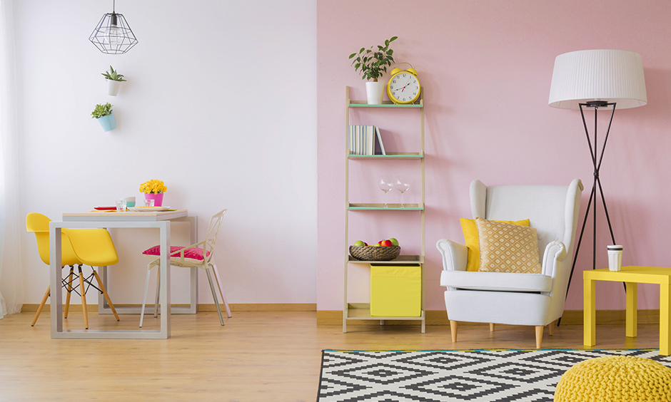 In this room white & pink, dual-wall paint colours segregate living & dining area look bright and cheerful