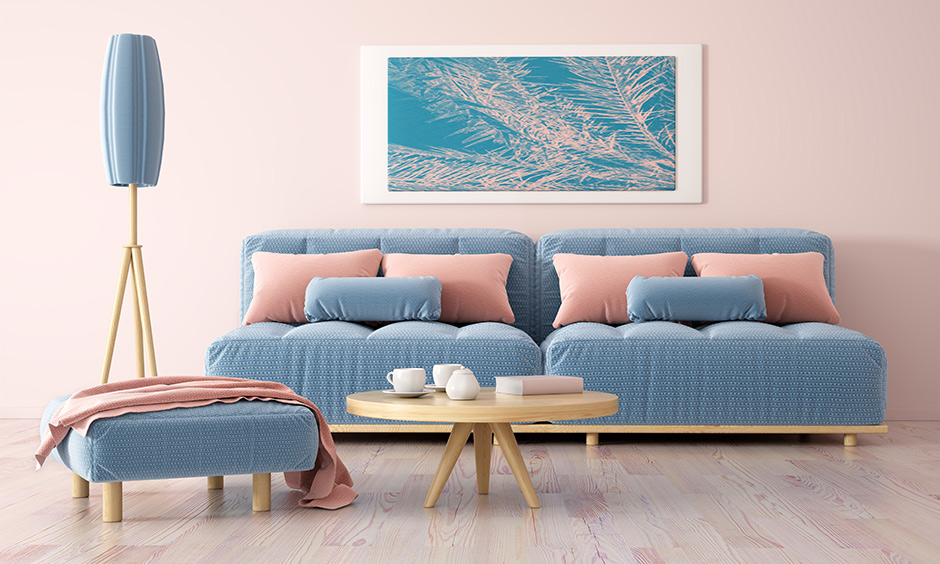 Pastel pink wall paint colour in this room with a blue sofa & pink pillow works fabulously.