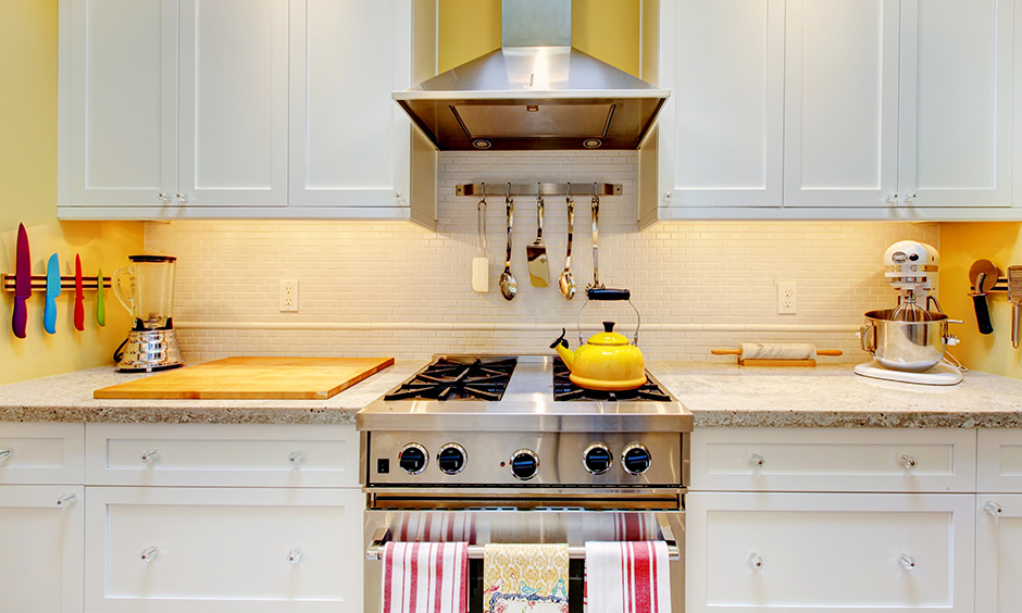Pastel yellow wall paint colour in the kitchen with all-white cabinetry is bright & stunning.