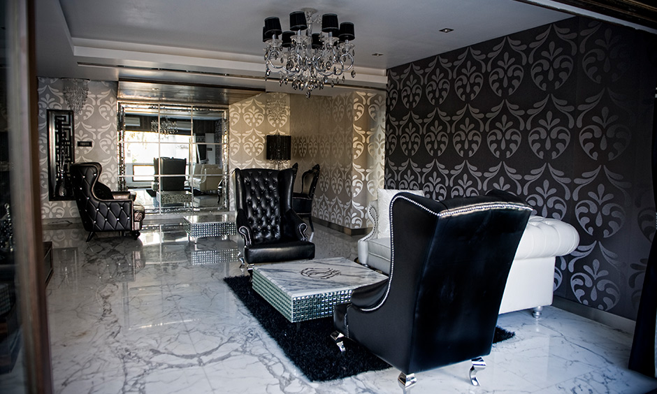 Living room pop plus minus which seamlessly incorporates a crystal chandelier amidst a dark colour scheme