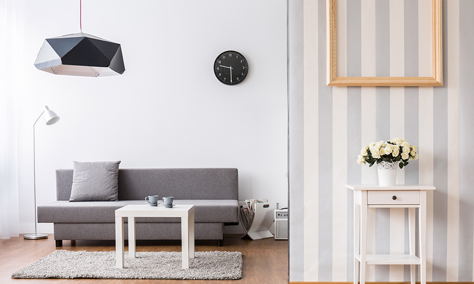 The striped wall paper design for hall with the empty frame and a small table is the perfect decor