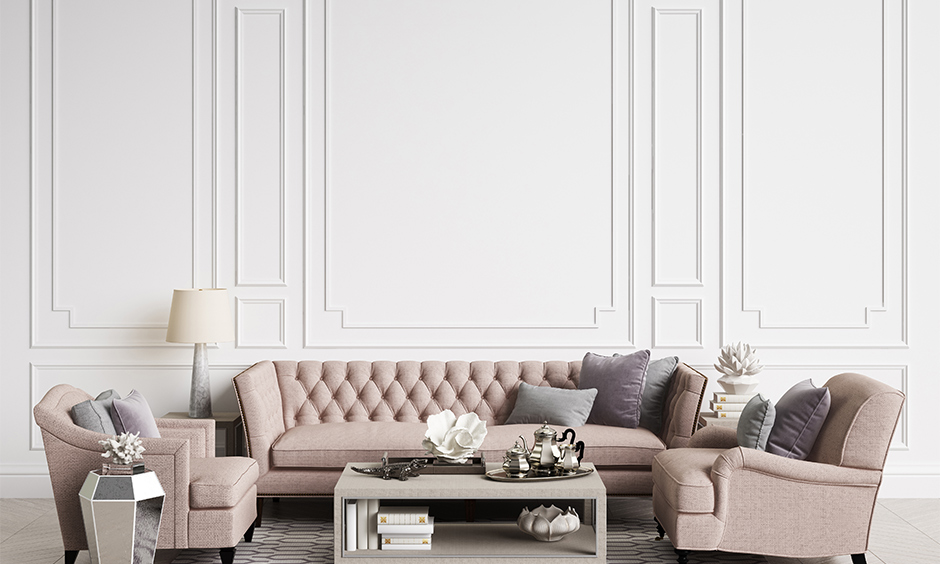 Beige coloured tufted sofa and two armchairs add a royal touch to the room is the best sofa design for small living room
