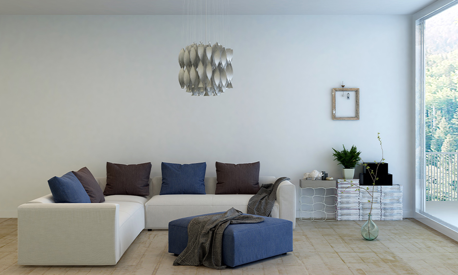 Modern living room l shape sofa in white colour with colourful pillows arranged right in the centre of the living room.