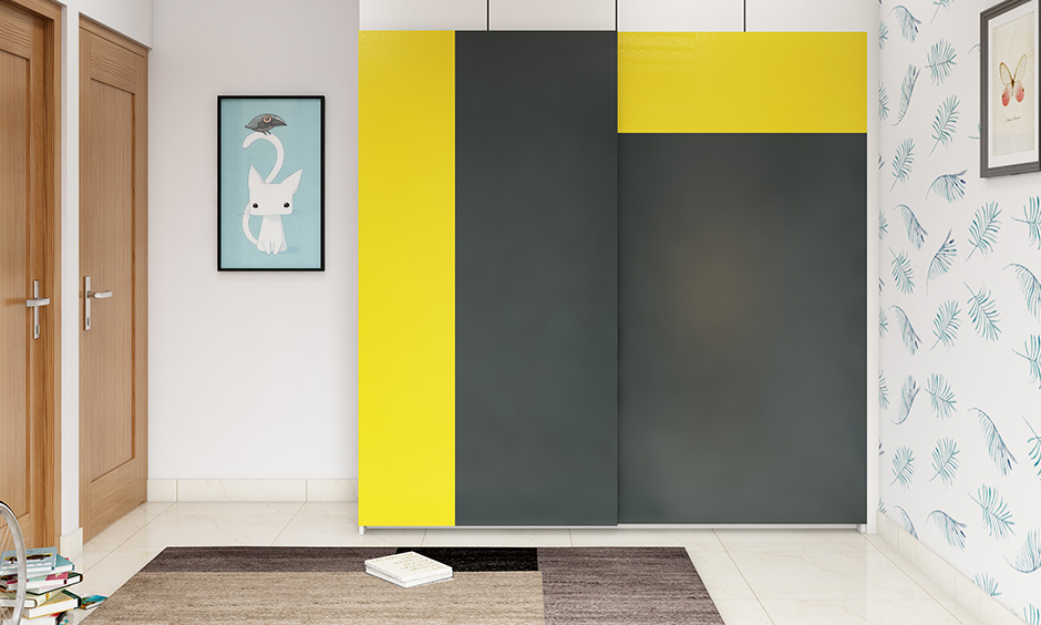 The bedroom has a bright yellow and grey double colour wardrobe design.