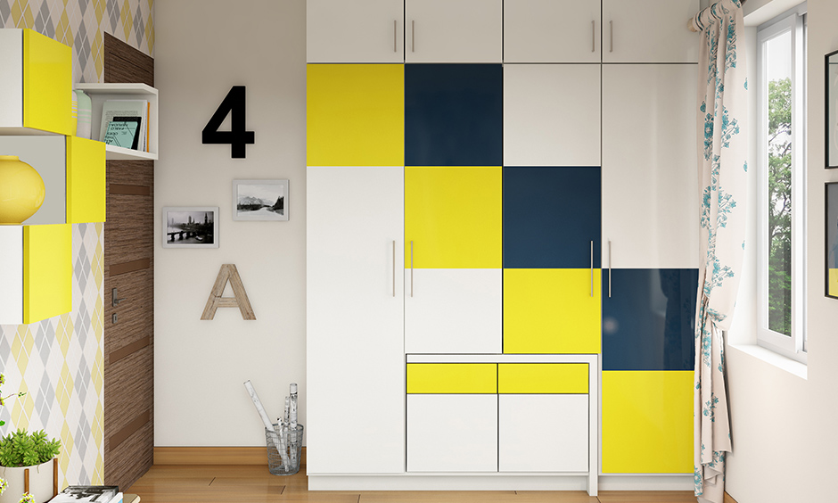 White coloured wardrobe with fun squares of dark teal and yellow laminates colour combination for wardrobe design.