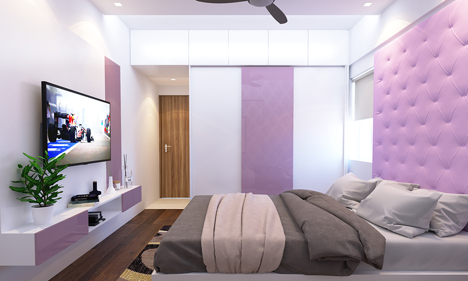 Glossy finish white and lilac wardrobe colour combination in this bedroom works well.