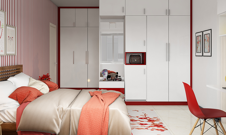 Bedroom wardrobe colour combinations in white & red on the border with a dressing table is a sleek design