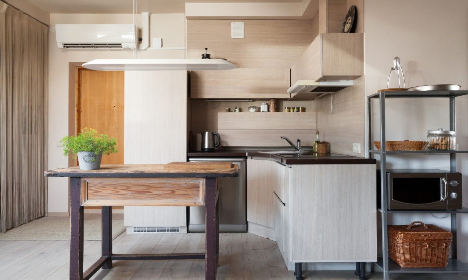Small island kitchen has a kitchen microwave carts and stands in grey placed at the corner.