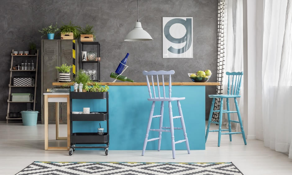 An island kitchen has a grey metal kitchen cart to store jars of spice and colourful tall stools.
