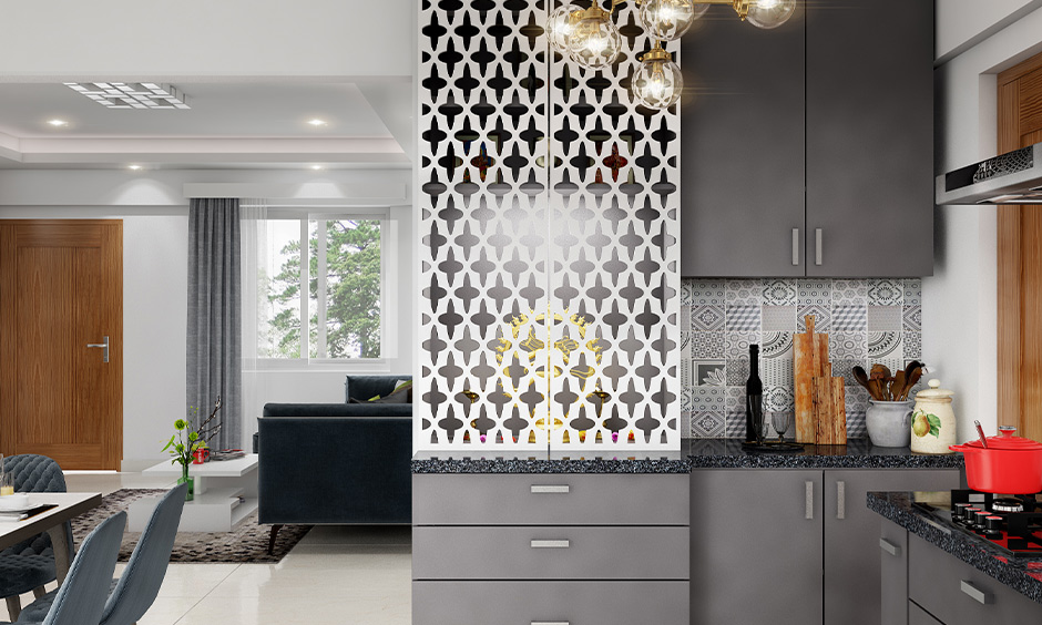 Pooja room in kitchen comes with a criss-cross pattern door made from white wood