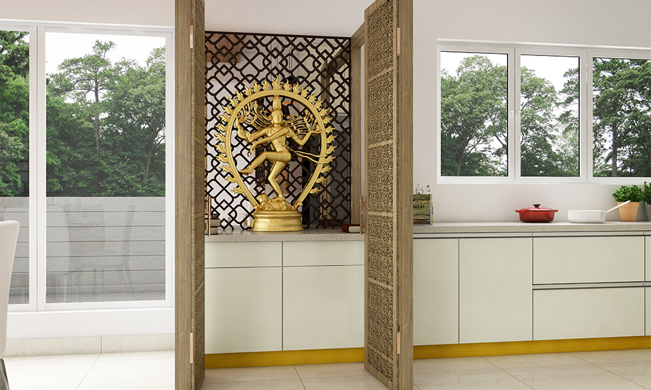 Pooja room in kitchen as per vastu comes with a tall unit and jali doors made from wood