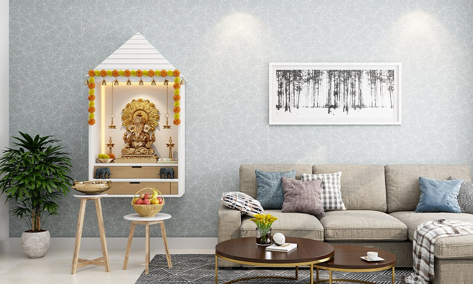 Mandir design in wall with bells, hooks to hang diya's and wood drawers to store pooja items