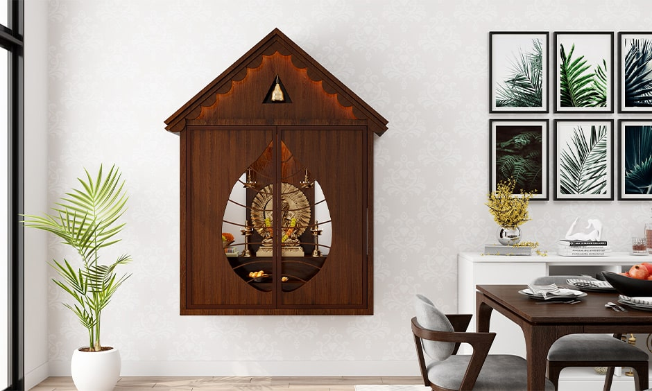 Simple wall mounted mandir design with dark wood doors in a leaf shape design
