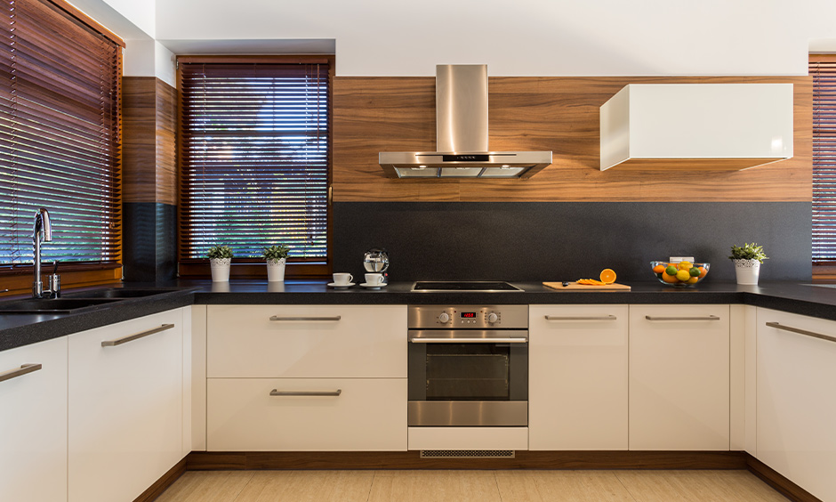 U-shaped modern white kitchen cabinets with black countertops bring a beautiful rustic touch to the area.