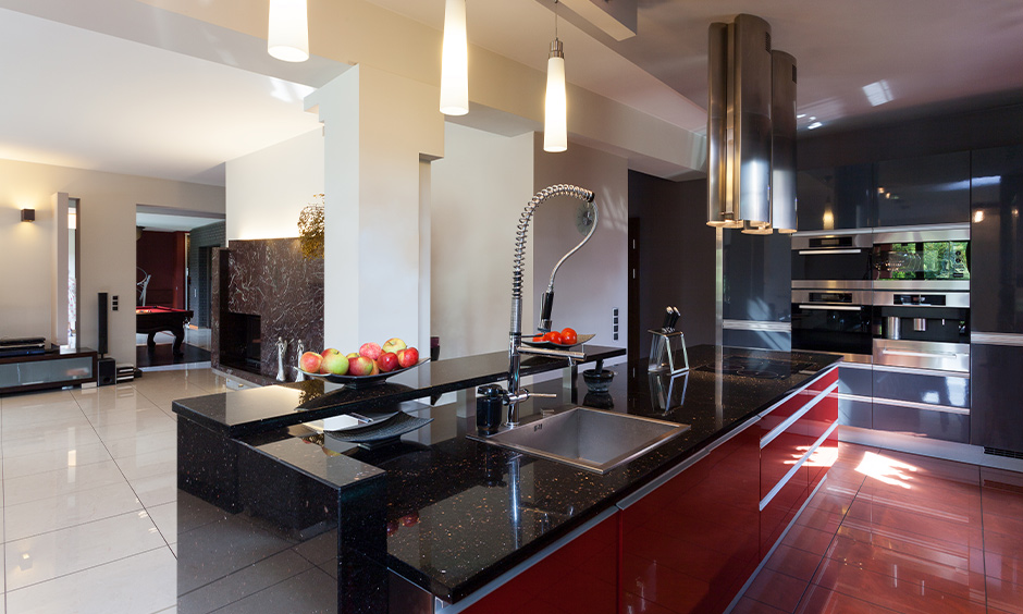 Black marble kitchen countertops with push to open drawers and cabinets in red lamination looks gorgeous.