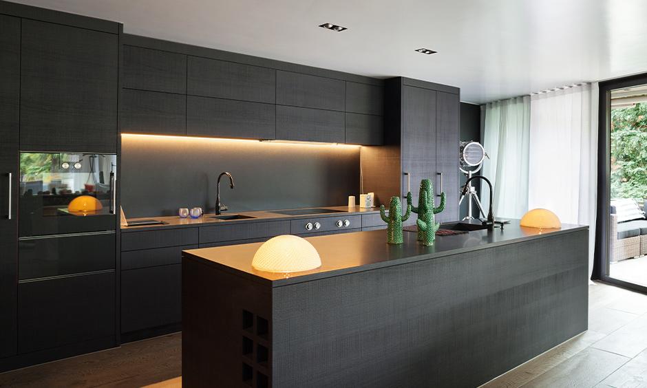 Black granite countertops kitchen in black with LED strip lighting at the backsplash is adorable.