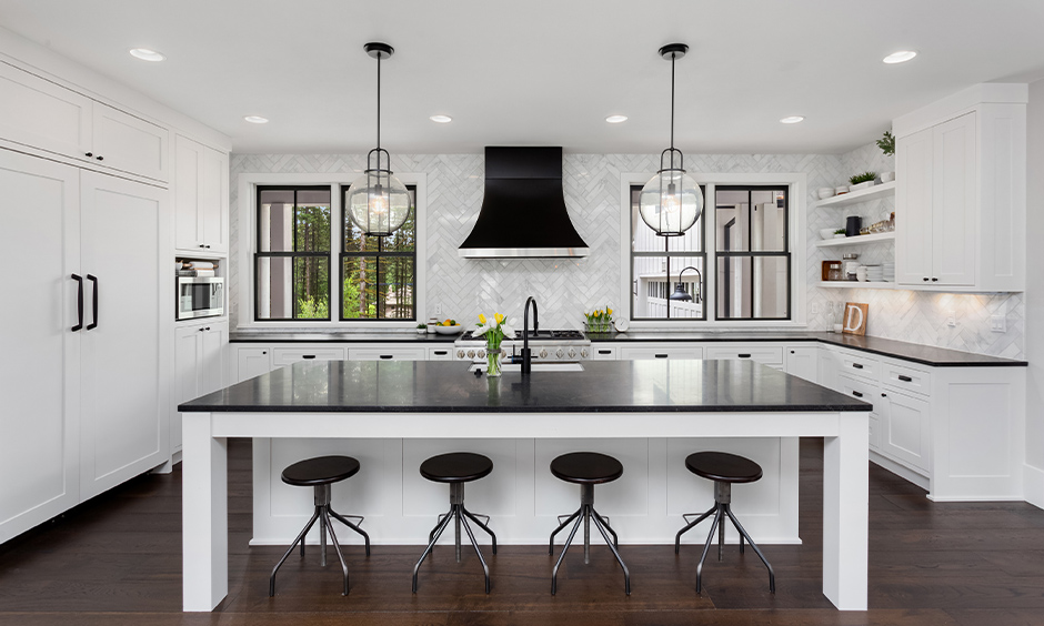 White island kitchen colour schemes with black countertops bring a modern touch to the kitchen.