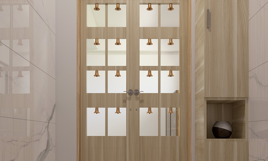 Simple pooja room door designs with glass which reflects more light in the pooja room