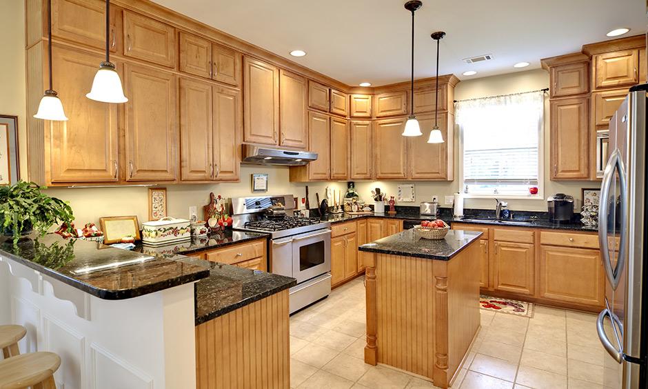 Glossy black granite countertops with cream white flooring make this kitchen look warm yet luxurious.