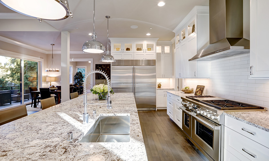 Modern white kitchen with granite countertops and backsplash in a brick pattern look luxurious and elegant.