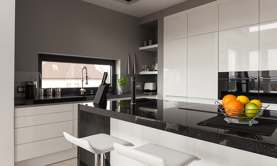 High glossy black granite countertops in kitchen with white cabinets and deep grey walls look stunning.