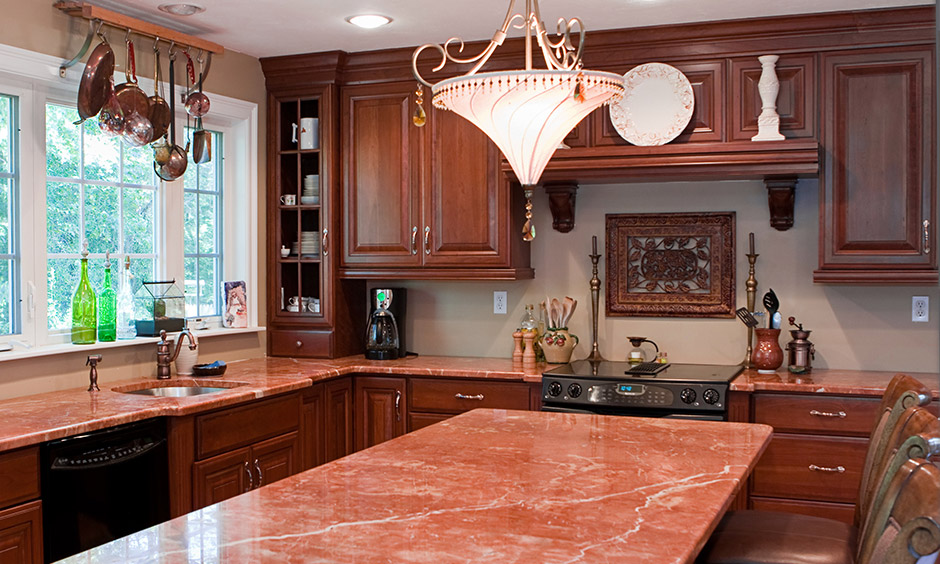 Stunning red granite countertops colour with deep oak brown cabinetry in the kitchen look rustic and cosy.