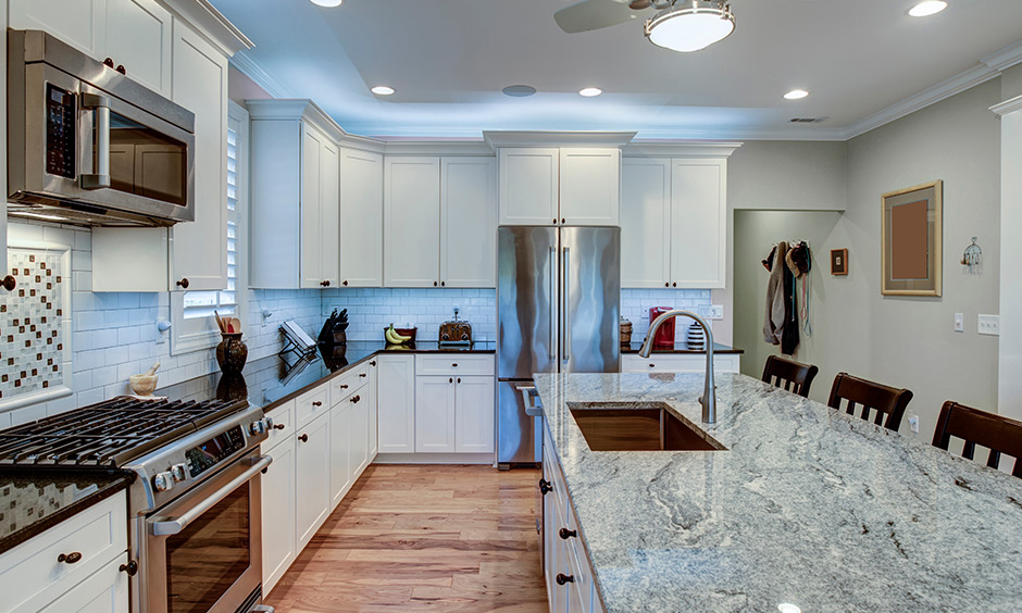 White granite countertops with a hint of grey in the white kitchen brighten and warm the hearts of your guests.