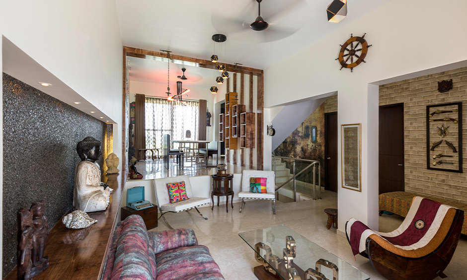 Modern living room designs Indian style with an olden day chair, coffee table, artefacts and a rustic touch.