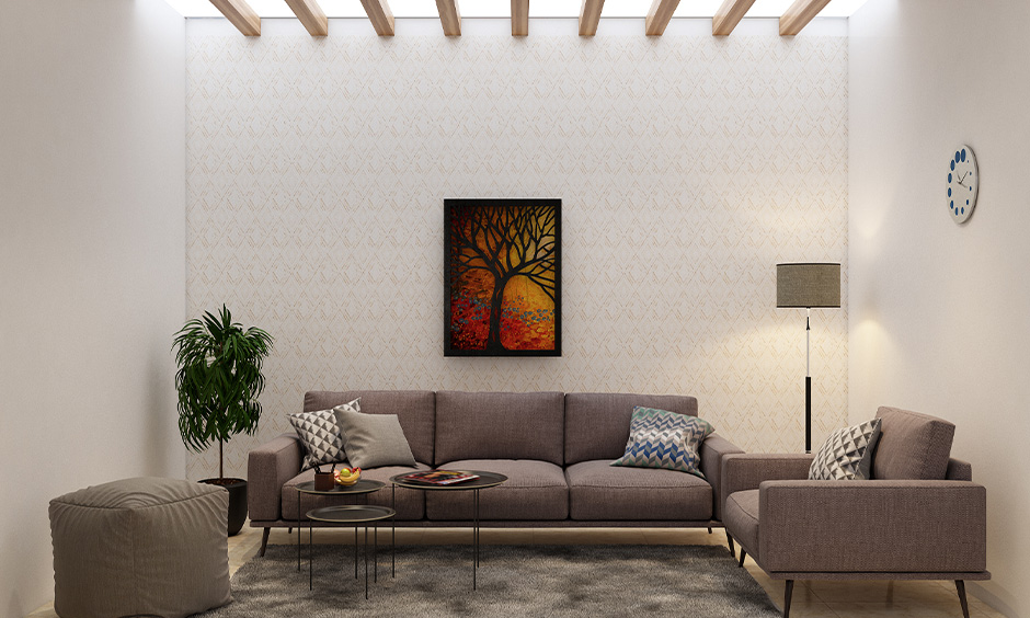 Old Bombay inspired modern living room design has a false ceiling, wooden panelling and wallpaper in a light yellow.