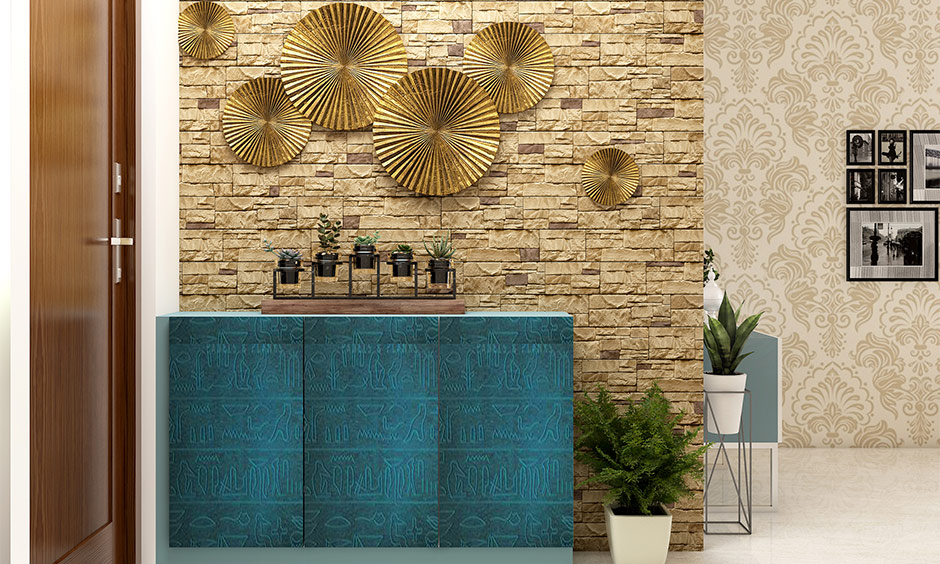 Traditional Indian home interior design hanged metallic decor items on the wall in the foyer in gold colour.