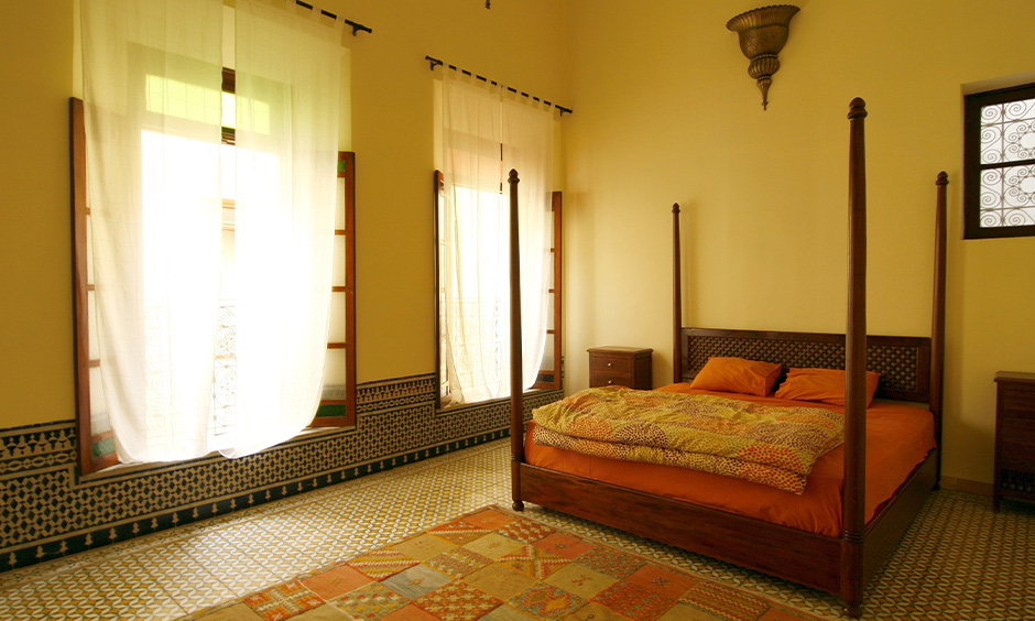 Moroccan mosaic floor tiles with the classic furniture, flowy drapes & natural light manage to infuse warmth to the bedroom.