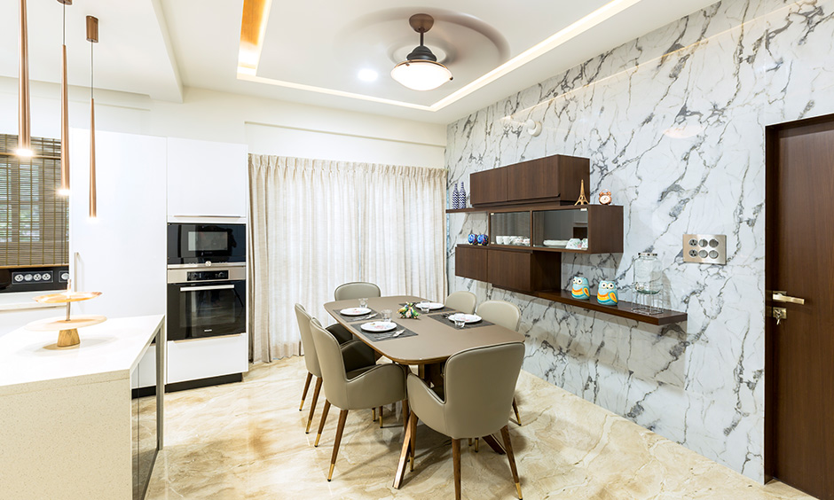 The dining cum kitchen area with dining table & wall-mounted crockery unit designed by best interior firms in Bangalore.