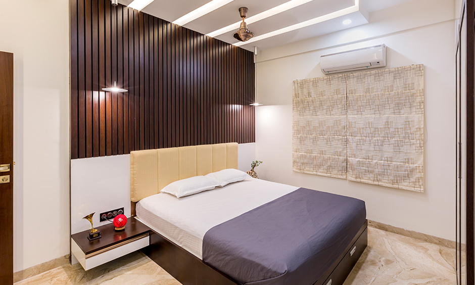 Interior design companies in Jayanagar designed this bedroom with a back panel in wooden rafters and a false ceiling.