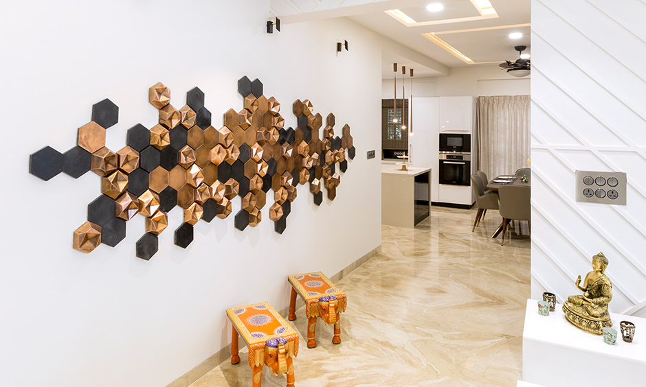 The foyer wall decor made with 3D tiles in black and rose gold designed by DC interior design firms in Jayanagar.