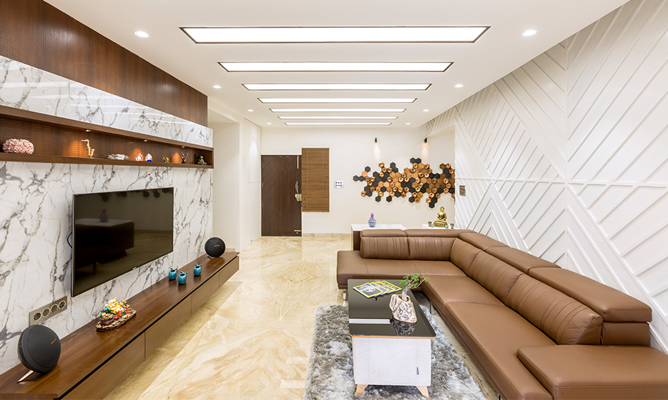 Uber-modern living room in white and brown colour theme has minimalist tv unit designed by interior firms in Bangalore.
