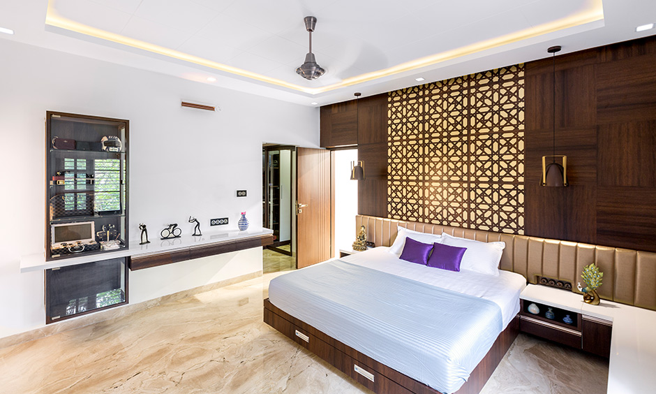 Master bedroom designed with a back panel in a jaali pattern and spotlights by interior design firms in Bangalore.