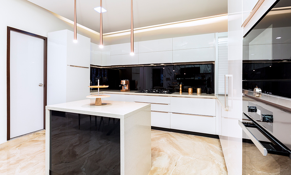 Best interior design firms in Bangalore designed this island kitchen in a white acrylic finish with cove light & LED lights.